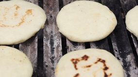 Toasted arepas cooking on the grill
