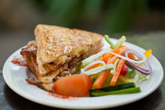 Toasted Bacon and egg sandwich with salad. A delicious toasted bacon and egg sandwich on a white plate with fresh salad Stock Photography