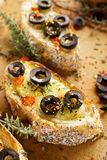 Toasted baguette with cheese, blck olives,chili pepper and thyme Stock Photo