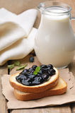 Toasted bread with blueberry jam and milk in glass jug Stock Images