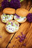 Toasted bread bruschetta with cream cheese and garlic edible flowers on olive wooden cutting board on stone slate gray background. stock images