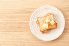 Toasted bread with butter curls on plate. Top view stock photography