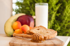 Toasted bread with honey and honey dipper and fruits Royalty Free Stock Photo