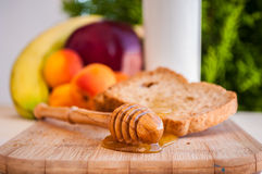 Toasted bread with honey and honey dipper and fruits Stock Photography