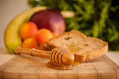 Toasted bread with honey and honey dipper and fruits Stock Images