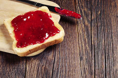 Toasted bread with jam. And knife on dark wooden table royalty free stock images