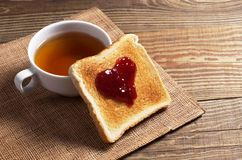 Toasted bread with jam and tea. Slice of toasted bread with raspberry jam in the shape of heart and a cup of tea on the old wooden table Royalty Free Stock Photos