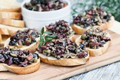 Toasted Bread with Mixed Tapenade Spread. Homemade mixed Olive Tapenade made with garlic, capers, olive oil, Kalamata, black and green olives spread over toasted stock image