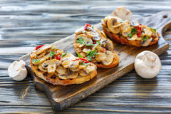 Crostini with mushrooms and onions on a wooden stand. Royalty Free Stock Image