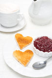 Toasted bread in the shape of heart with berry jam and coffee Royalty Free Stock Image