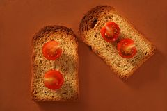 Toasted bread slices and cherry tomatoes Royalty Free Stock Images