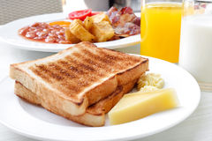 Toasted bread and some food food for breakfast. Various kinds of food for breakfast including toasted bread, cheese, butter, milk, orange juice etc royalty free stock photo