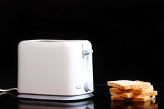 Toasted bread and toaster. Over dark marble Royalty Free Stock Photo