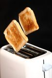 Toasted bread and toaster. Over dark marble Royalty Free Stock Image