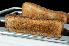 Toasted bread and toaster. Closeup of toasted bread and toaster on black background Stock Image