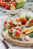 Toasted bread topped (Bruschetta) with grilled zucchini, mozzarella, cherry tomatoes. Italian cuisine. Stock Photo
