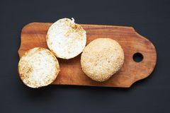 Toasted burger buns with sesame seeds on wooden board. Fast food. Top view. royalty free stock photography