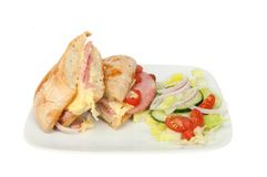 Toasted ciabatta with salad. Toasted cheese, ham and tomato in a ciabatta roll with salad on a plate isolated against white Stock Images