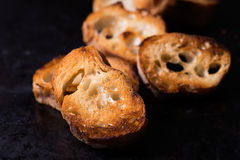 Toasted crusty baguette  on old black background Royalty Free Stock Photos
