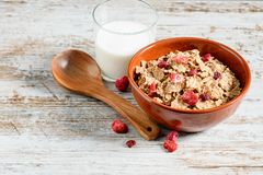 Toasted dietetic flakes of rice with fruits. Dietetic flakes of rice with dry fruits in the bowl and a glass of milk on the white background royalty free stock photography