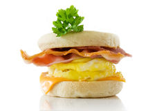 Toasted English Bacon & Egg Muffin. Bacon & egg cheese muffin with a sprig of green parsley stock photo