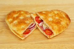 Toasted focaccia snacks. Toasted cheese, ham, tomato and onion focaccia flatbreads on a wooden chopping board royalty free stock photos