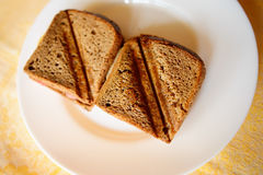 Toasted ham and cheese sandwich. On a white circular plate Royalty Free Stock Photo
