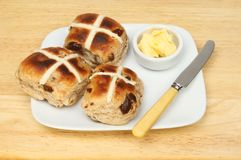 Toasted hot cross buns. On a plate with butter and a butter knife on a wooden tabletop Stock Images