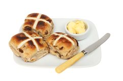 Toasted hot cross buns. On a plate with butter and a butter knife isolated against white Royalty Free Stock Image