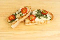 Mozzarella and tomato ciabatta. Toasted mozzarella, tomato and basil ciabatta bread on a wooden chopping board Stock Photo