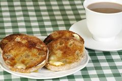 Toasted muffins. Toasted english muffins and tea on a green gingham cloth Royalty Free Stock Photos