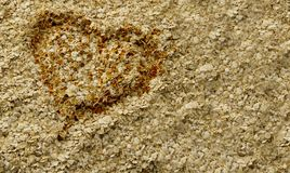 Toasted Oat Heart Background. Golden toasted oat heart surrounded by oatmeal. Background. Horizontal Royalty Free Stock Images