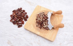 Toasted pecans with a rocking knife. Whole toasted pecans with a rocking knife chopping the nuts on a board Royalty Free Stock Photo