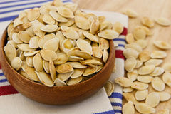 Toasted pumpkin seeds overflowing a wooden bowl Royalty Free Stock Image