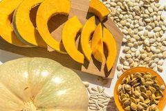 Toasted pumpkin seeds with raw seeds and pumpkin on a white table. royalty free stock photos