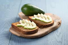 Toasted rye bread with sliced avocado and herbs Royalty Free Stock Image