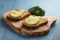 Toasted rye bread with sliced avocado and herbs Royalty Free Stock Photos