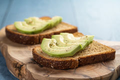 Toasted rye bread with sliced avocado and herbs Royalty Free Stock Photo