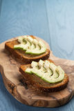 Toasted rye bread with sliced avocado and herbs Royalty Free Stock Images