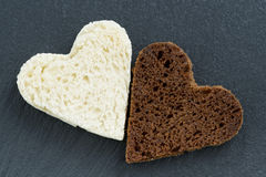 Toasted rye and white bread in the form of heart on dark Royalty Free Stock Photos
