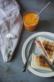Toasted sandwich with orange carrot smoothie on table with flower and napkin Royalty Free Stock Photography