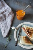 Toasted sandwich with orange carrot smoothie on table with flower and napkin Royalty Free Stock Photos