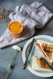 Toasted sandwich with orange carrot smoothie on table with flower and napkin Stock Photo