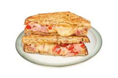 Toasted sandwich on a plate. Toasted cheese, ham and tomato sandwich on a plate isolated against white Stock Photography