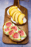 Toasted sandwiches with cream cheese fresh ripe green and red figs and peaches. Drizzled with honey. Wholegrain rye bran bread. On wood cutting board, grey Stock Photography