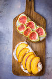 Toasted sandwiches with cream cheese topped with fresh ripe figs and peaches. Drizzled with honey. Wholegrain rye bran bread. On wood cutting board, grey Royalty Free Stock Image