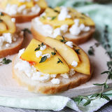 Toasted wheat bread with ripe peaches Royalty Free Stock Photography