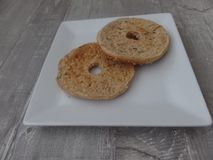 Toasted wholemeal bagel on a white plate stock photos