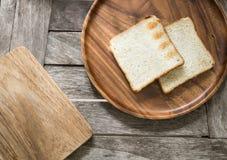 Toasten Sie Brot auf hölzerner Platte und hölzernem Brotschneidebrett Lizenzfreie Stockfotos