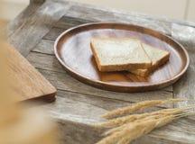 Toasten Sie Brot auf hölzerner Platte und hölzernem Brotschneidebrett Lizenzfreies Stockfoto